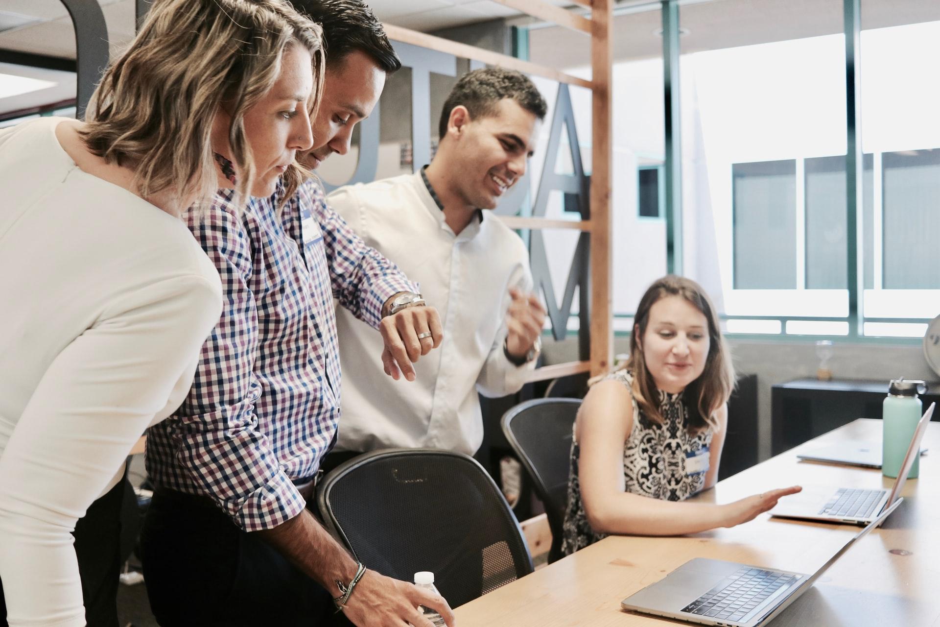 Kaksi naista ja kaksi miestä työpöydän ääressä