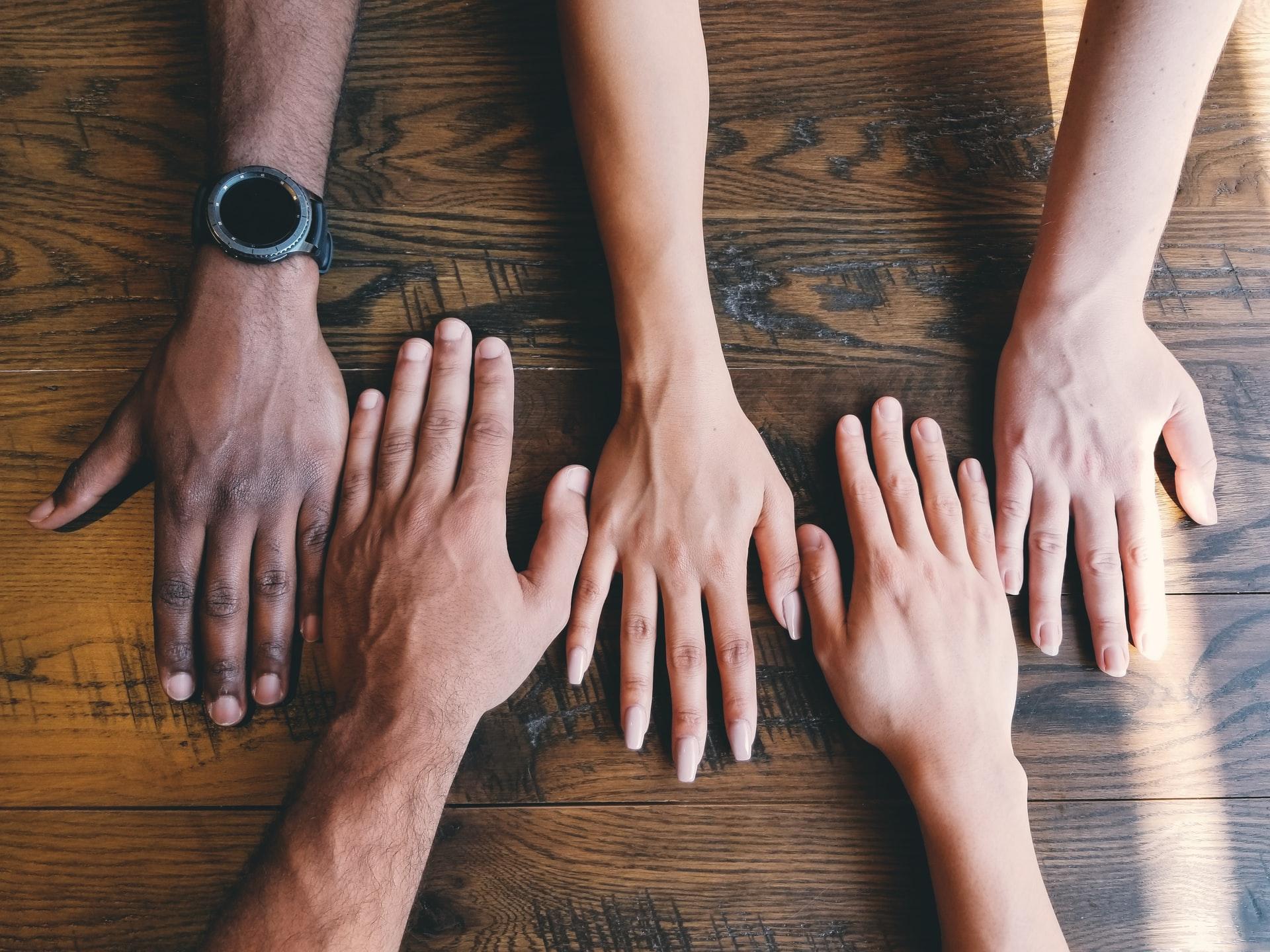 Neljä kättä vierekkäin pöydällä