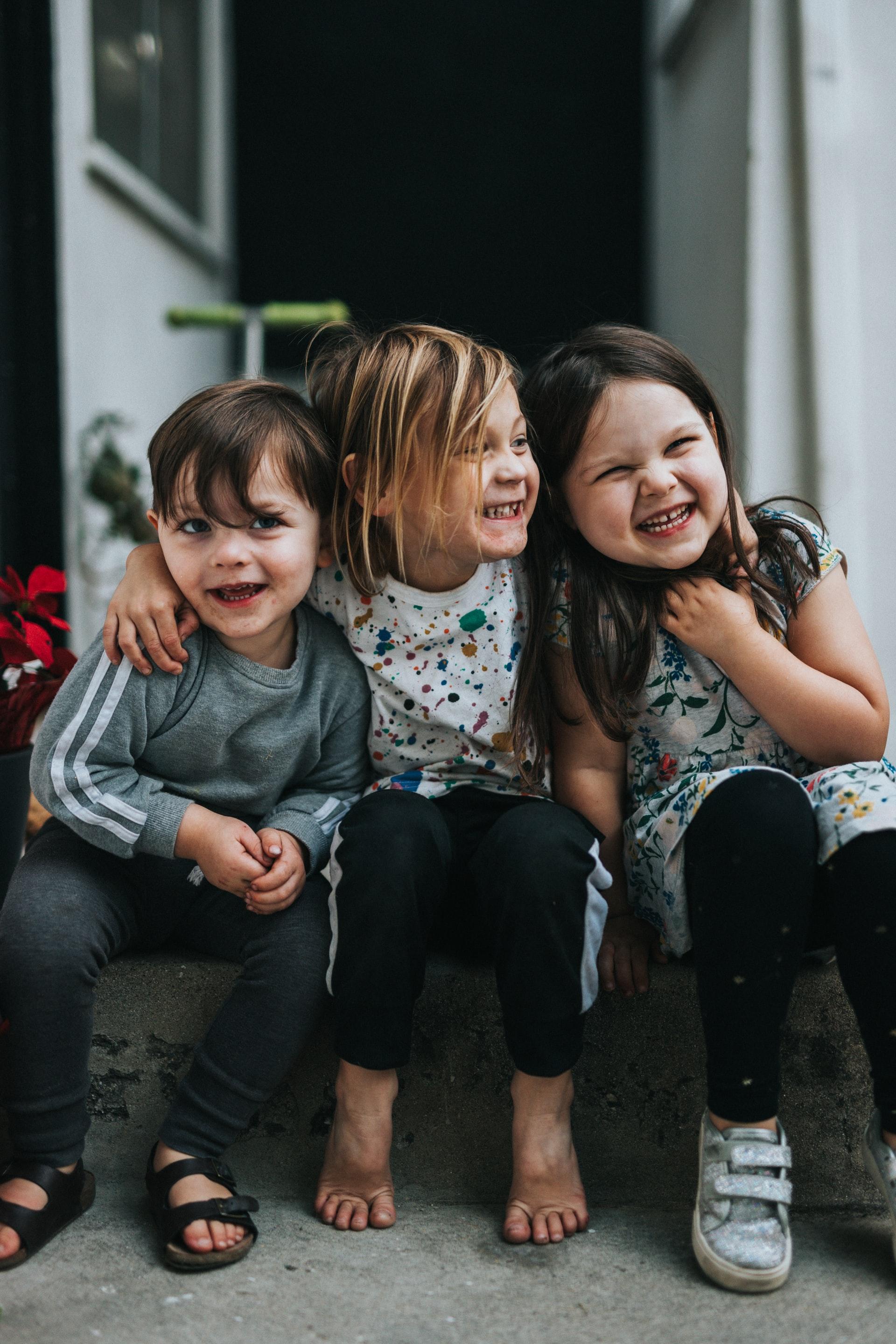 kolme nauravaa lasta istuu portailla