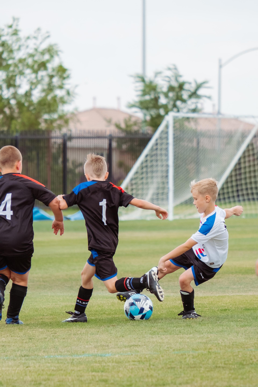 kolme lasta pelaamassa jalkapalloa