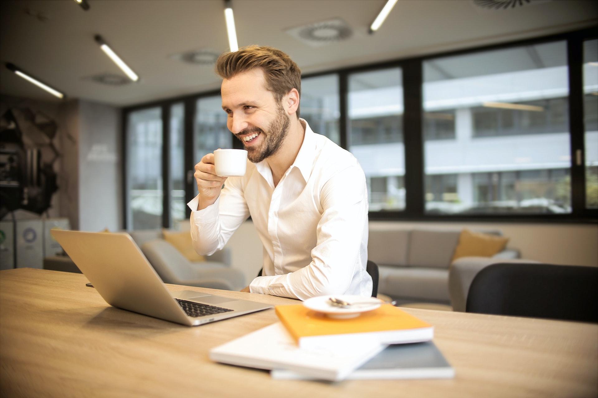 Valkopaitainen mies työpöydän ääressä kahvikuppi kädessään