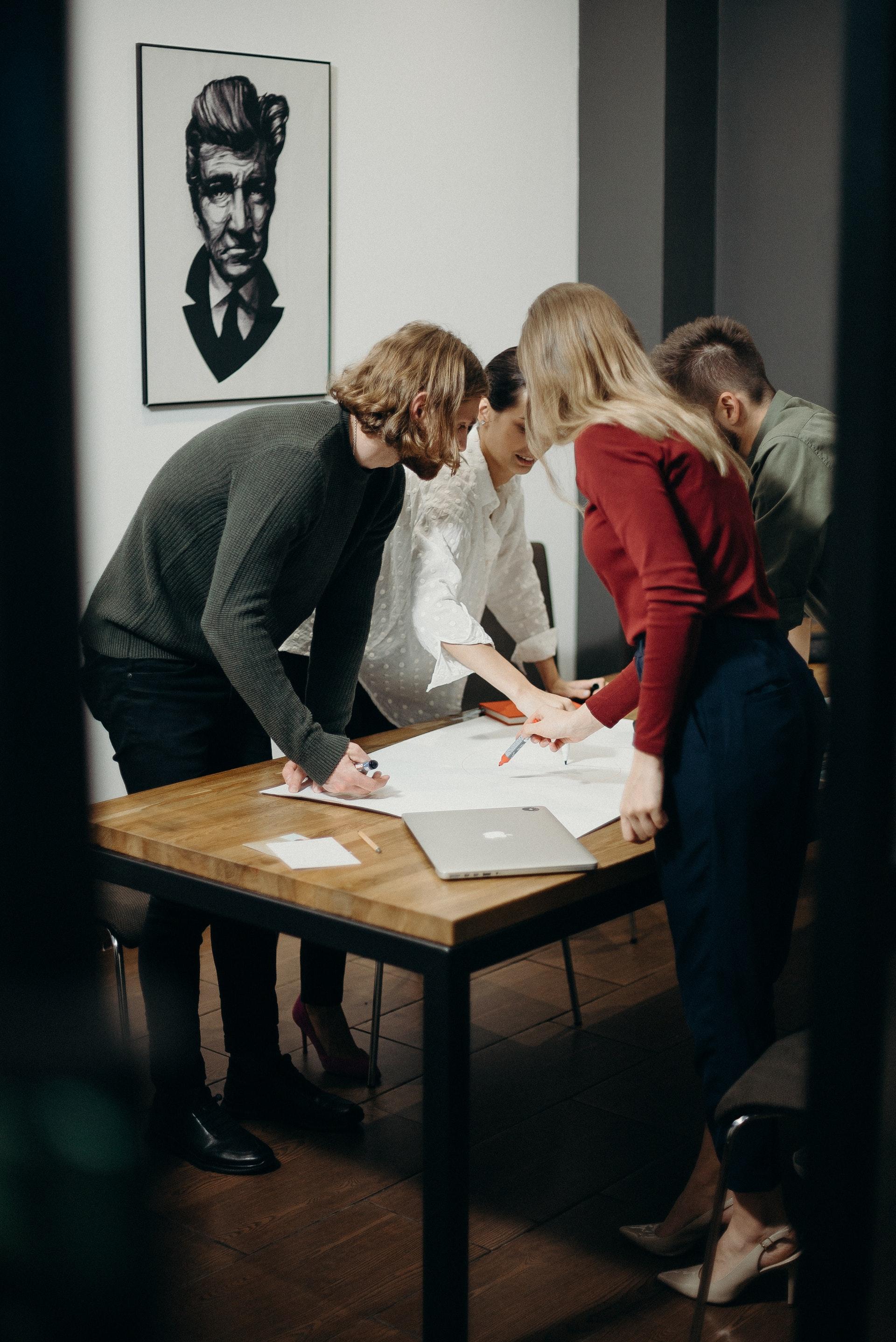 Neljä ihmistä työpöydän ääressä