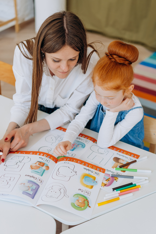 Nainen ja lapsi pöydän ääressä lukemassa oppikirjaa